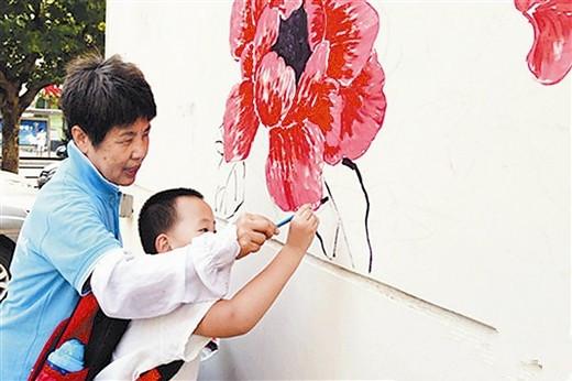 绘画墙体画,共建幸福家园.(图片来源:大连日报)-绘墙画 庆国庆